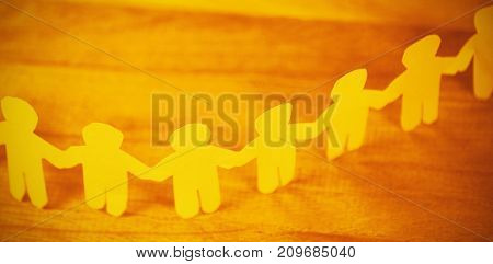 High angle view of paper cut out figures forming chain on wooden table