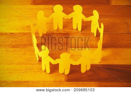 High angle view of yellow paper cut out figures formimg circle on wooden table