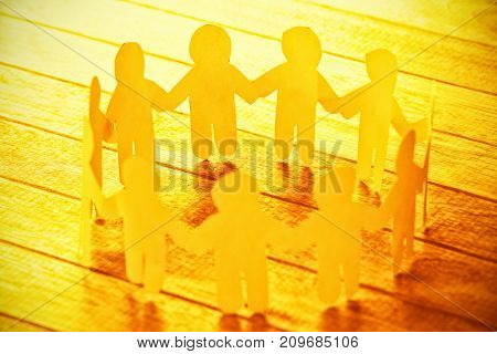 High angle view of yellow paper figures forming circle on wooden table