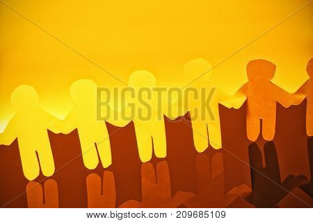 High angle view of Yellow paper cut out figures making chain with reflection on glass table