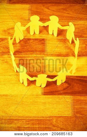High angle view of yellow paper cut out figures formimg circle on table