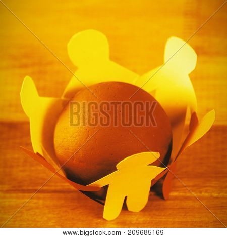 High angle view of multi colored paper cut out figures forming circle around ball on table