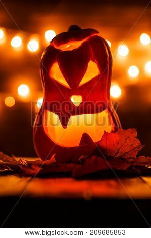 Image of halloween pumpkin cut in shape of face on background with burning yellow lights