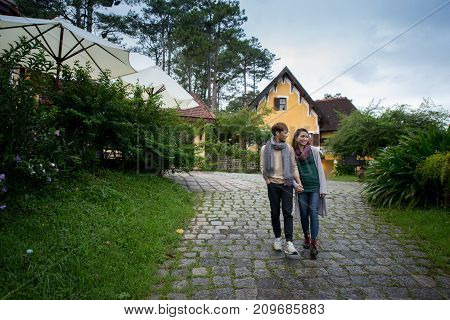 Young Vietnamese couple in love walking on hotel territory