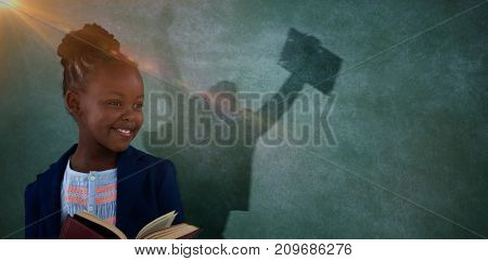 Businessman jumping while holding briefcase against businesswoman reading book against blackboard