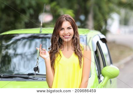 Beautiful young woman with key near car
