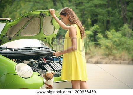 Young woman with dog standing near broken car