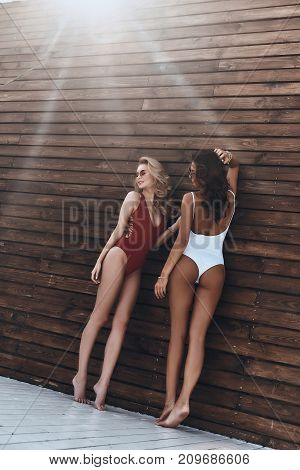 Women of your dreams. Full length of two attractive young women in swimwear smiling while standing against the wooden wall outdoors