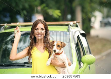 Beautiful young woman with key and cute dog near car