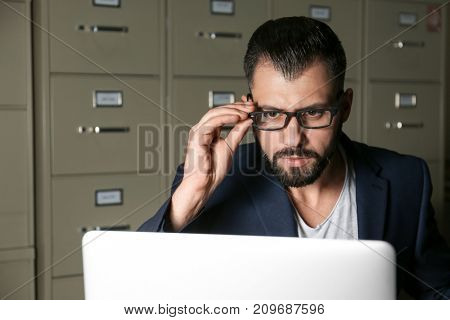 Young man working with laptop at table in archive