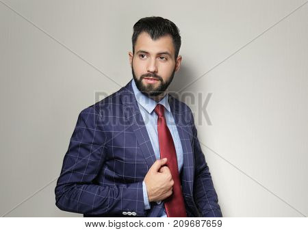 Handsome successful businessman on light background