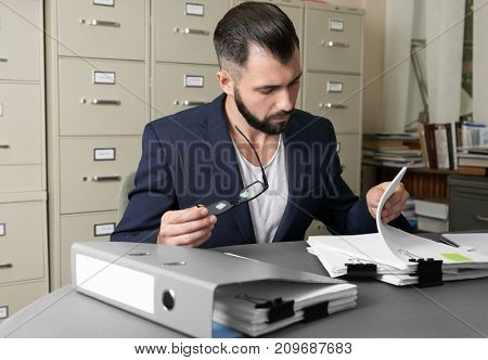 Young man working with documents at table in archive