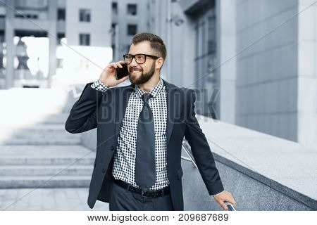 Handsome successful businessman talking on mobile phone outdoors