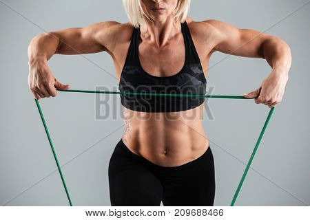 Cropped image of a muscular adult sportswoman holding stretching band isolated over gray background