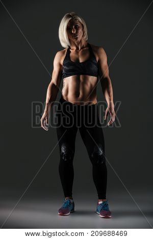 Full length portrait of an exhausted attractive muscular sportswoman standing and resting isolated over gray background