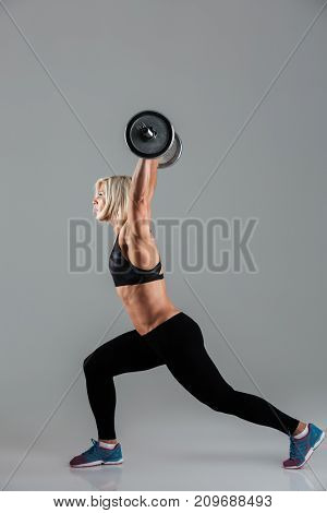 Side view portrait of a strong muscular adult sportswoman lifting a heavy barbell isolated over gray background