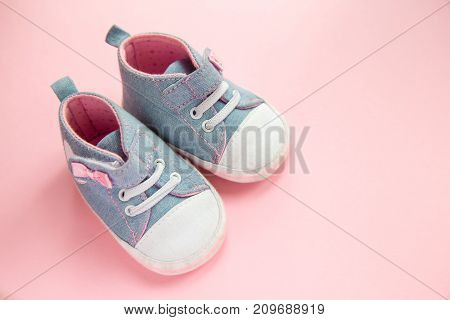 Children's denim sports shoes for girls, stands on a pink background. closeup view from the top. the concept of children's clothing