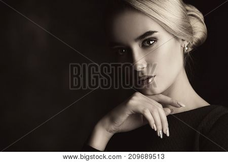 Portrait of a beautiful elegant young woman wearing black dress. Beauty, fashion concept. Make-up and cosmetics. Studio shot. Black background.