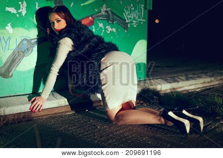 Sexy glamorous trendy caucasian woman kneeling at wall