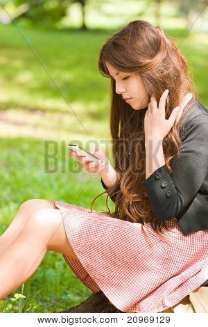 Attractive Girl With Phone In Park