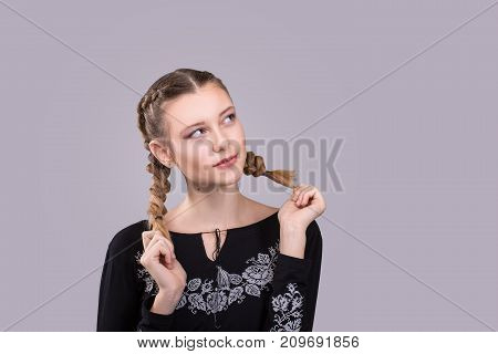 young woman with stylish hairstyle pigtails. Expressive girl in a black embroidery looks up on grey background