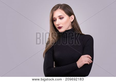 Beauty portrait of young attractive woman with agressive make-up over gray background