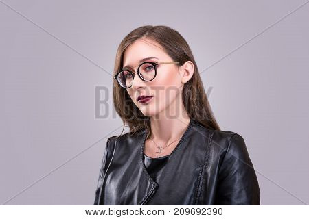 Beauty portrait of young attractive woman wearing glasses with agressive make-up dressed in black leather jacket over gray background
