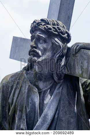 The road to Golgotha. Ancient statue of Jesus Christ carrying the Holy Cross. (holy faith religion god suffering concept)
