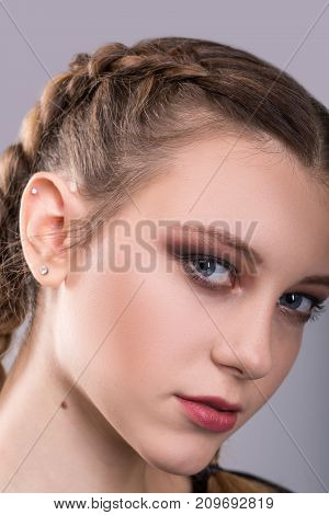 closeup portrait of a teenage girl with braided pigtails standing in front of a and gray background looking at the camera