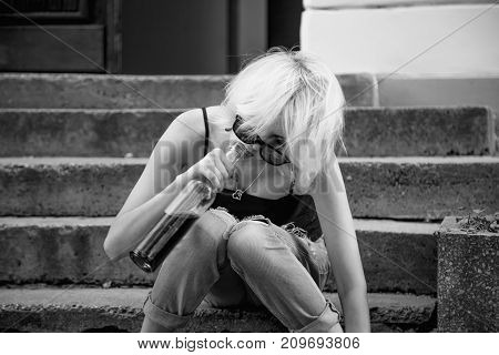 Young female with alcoholic drink looking very sad and depressed. Drunk young people (alcoholism pain pity hopelessness social problem of dependence concept)