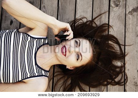 Young woman get very good news on phone and get very happy. (Gestures body language psychology concept)