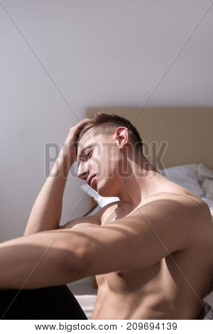 Depressed man sitting nearby bed concept. Alone with problems at home