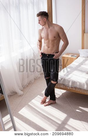 Handsome topless healthy man thinking nearby window concept. White room interior. Sunny morning at home