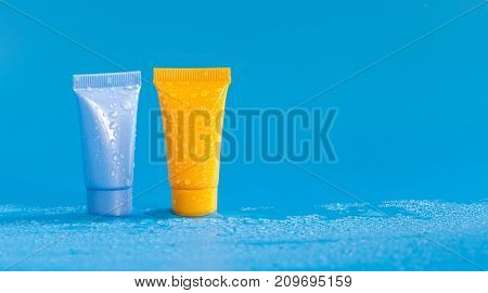 Abstract colorful cosmetic tubes in droplets of water. Refreshing hygiene medicine supplies, orange blue color plastic containers. Close-up photo, copy space photography.