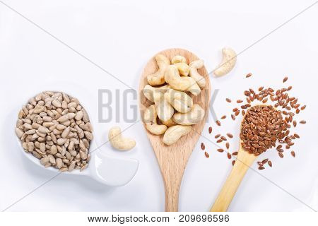 Healthy food concept top view sunflower seeds, cashew nuts and flax seeds on white background