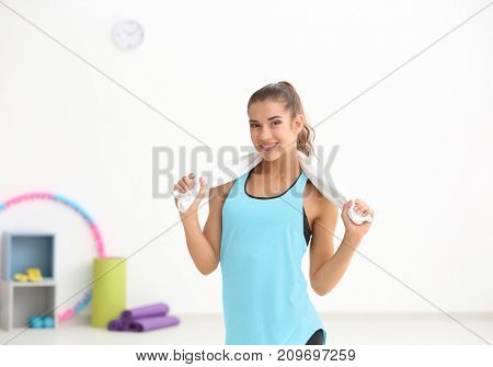 Young sporty woman with towel in gym