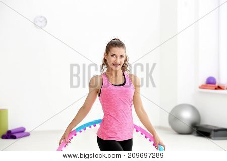 Woman with hula hoop in gym