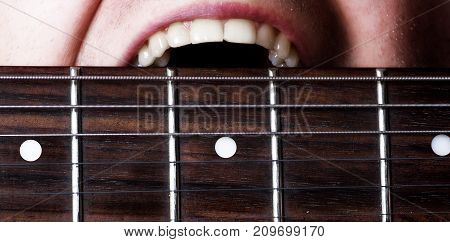 musician guitarist clenches his electric guitar with his teeth white smile the concept of strong healthy teeth macro close up