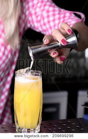 The girl bartender makes a cocktail pours it into a glass standing on the bar. Female hands prepares a drink in the nightclub. Concept work in a club