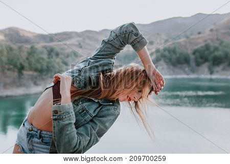 Woman in jacket posing in nature with a lake in the background