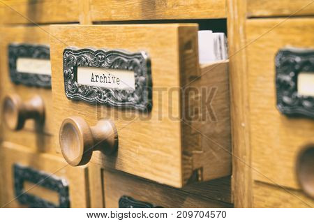 The Archives Card Catalog old wooden file catalog box index database archive and library concept.