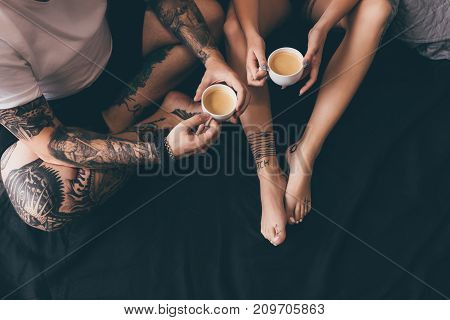 Couple With Cups Of Coffee In Bed