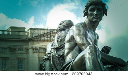 Bronze sculpture representing Art and Science with Buckingham Palace in the background on the Queen Victoria Memorial London UK