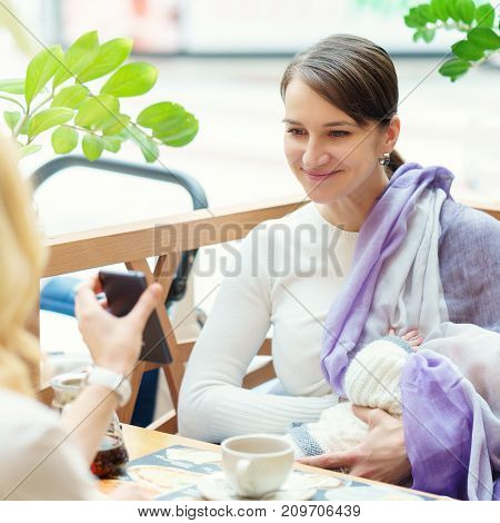 Young European Gay Couple Or Friends Women With Infant Is Sitting On Bench Close To White Baby Carri