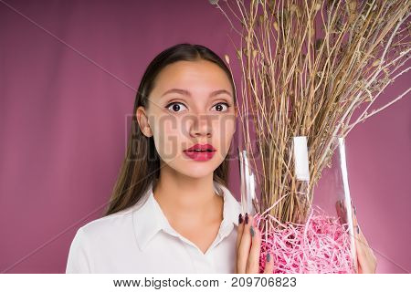 A girl with big eyes holds a vase with dry twigs in her hands and looks directly into the camera