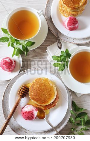 Two portions of banana pancakes with honey and fruit sorbet and cups of green coffee top view