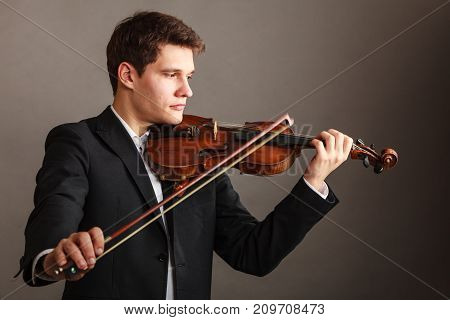 Music passion hobby concept. Young man man dressed elegantly playing on wooden violin. Studio shot on dark background