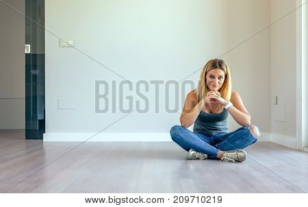 Thoughtful blonde girl sitting in a empty living room