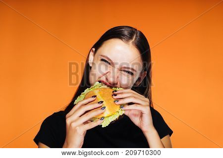 hungry girl sits on a diet, but eats an unhealthy high-calorie hamburger