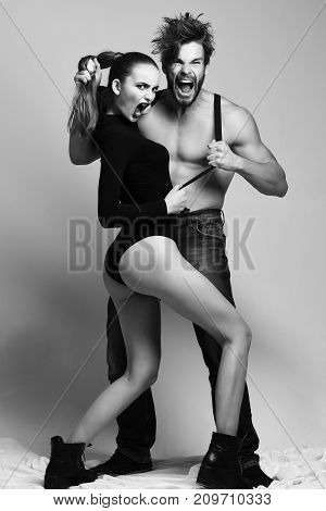 Angry bearded man with beard wearing suspenders on muscular torso and jeans keeping hair ponytail of pretty girl or sexy woman with blue lips in black bodysuits shouting on grey background